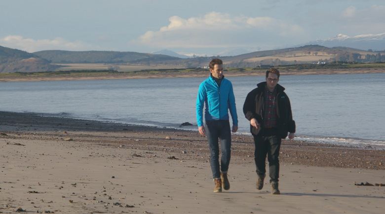Two men walking along a beach. Snow-capped mountains can be seen across the water in the background.