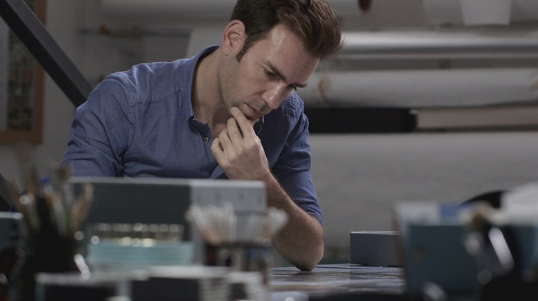 A man, deep in concentration, working at a desk.