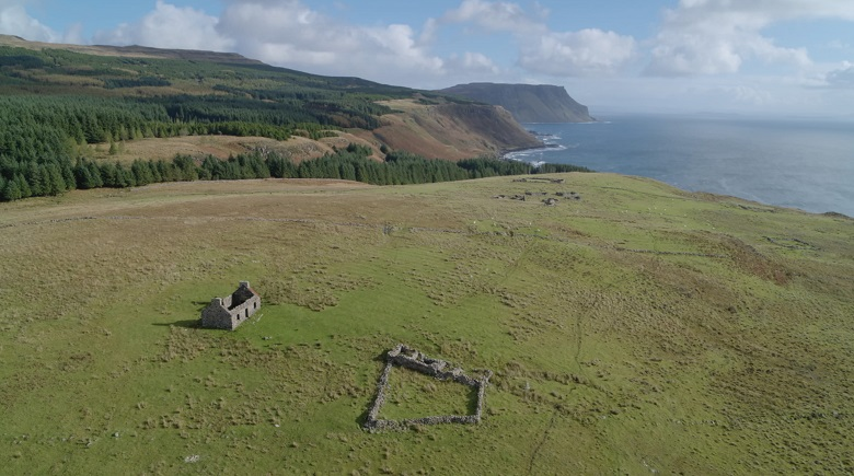 An abandoned cottage and traces of other ruined buildings located in a remote clearing flanked by forest and sea