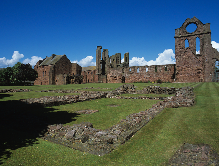 A view of Arbroath Abbey on a sunny day. The distinctive 'Round O' circular window can be seen in a tower.