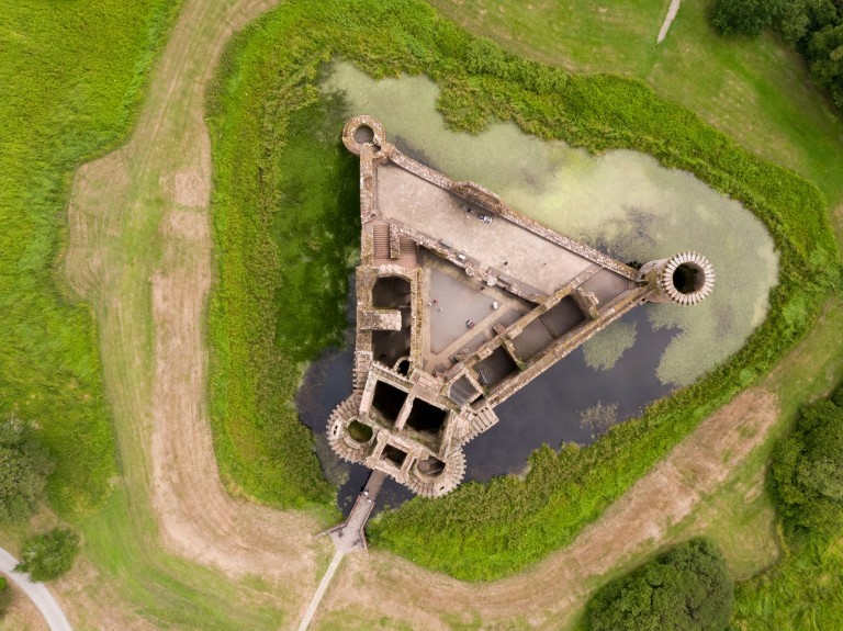 A drone photo of Caerlaverock Castle clearly showing its distinctive triangular shape. It is surrounded by a moat and accessed by bridge.