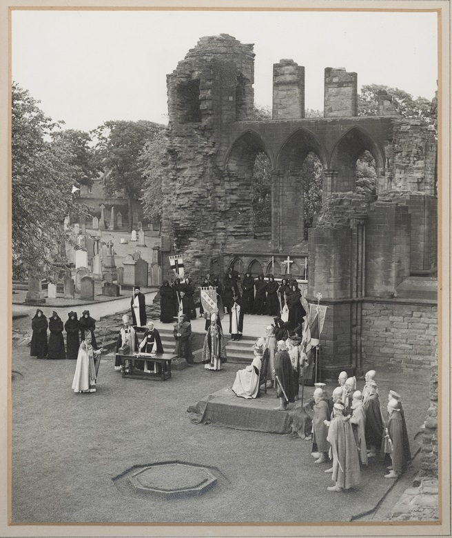 Costumed re-enactors perform a ceremony inside the ruin of Arbroath Abbey