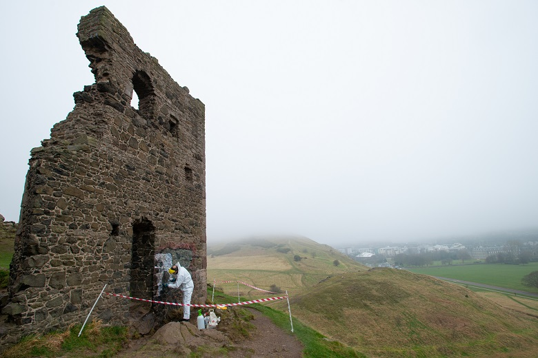 A worker in white protective overalls works to clear graffiti from a historic ruin.