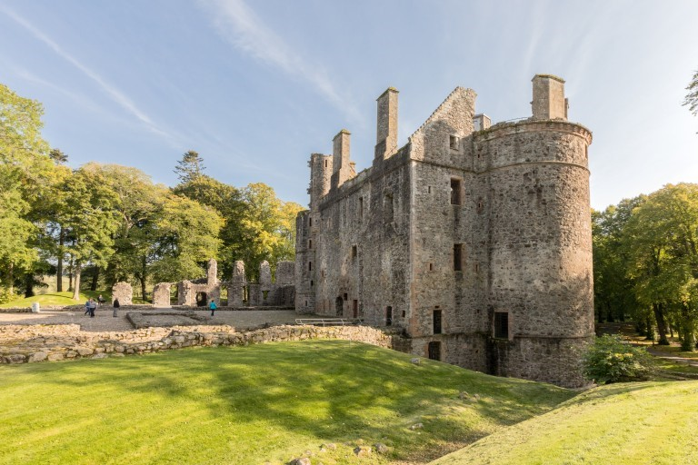 A shot of Huntly Castle in the sunshine. Visitors can be seen exploring the ruins.