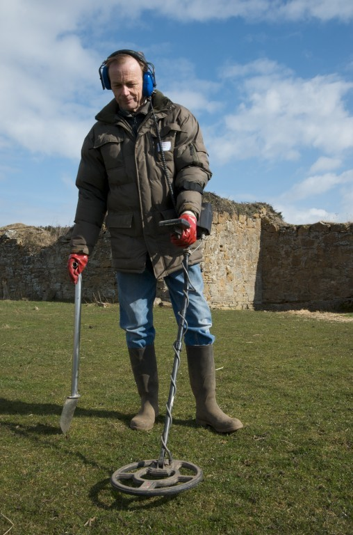 A man metal detecting at a historic ruin