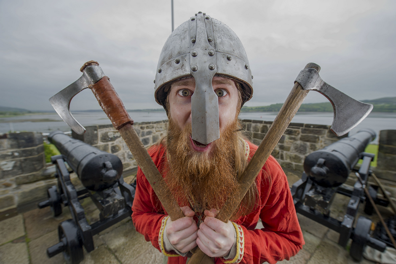 A bearded man wearing a metal helmet faces the camera with an axe in each hand