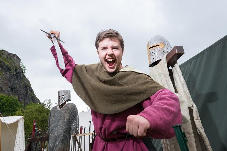 A reenactor in medieval clothing brandishing a sword