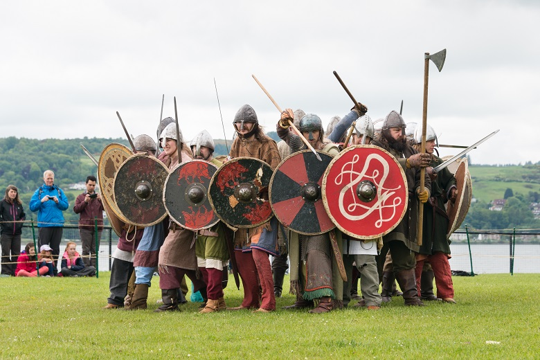 A group of reenactors dressed as Vikings in a battle formation. They are armed with swords, axes and colourful round shields.