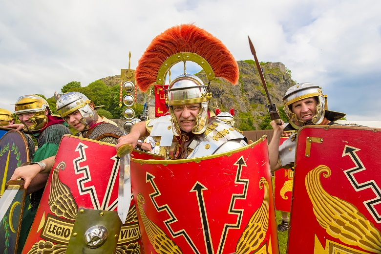 Reenactors dressed as Romans pose in front of Dumbarton Rock