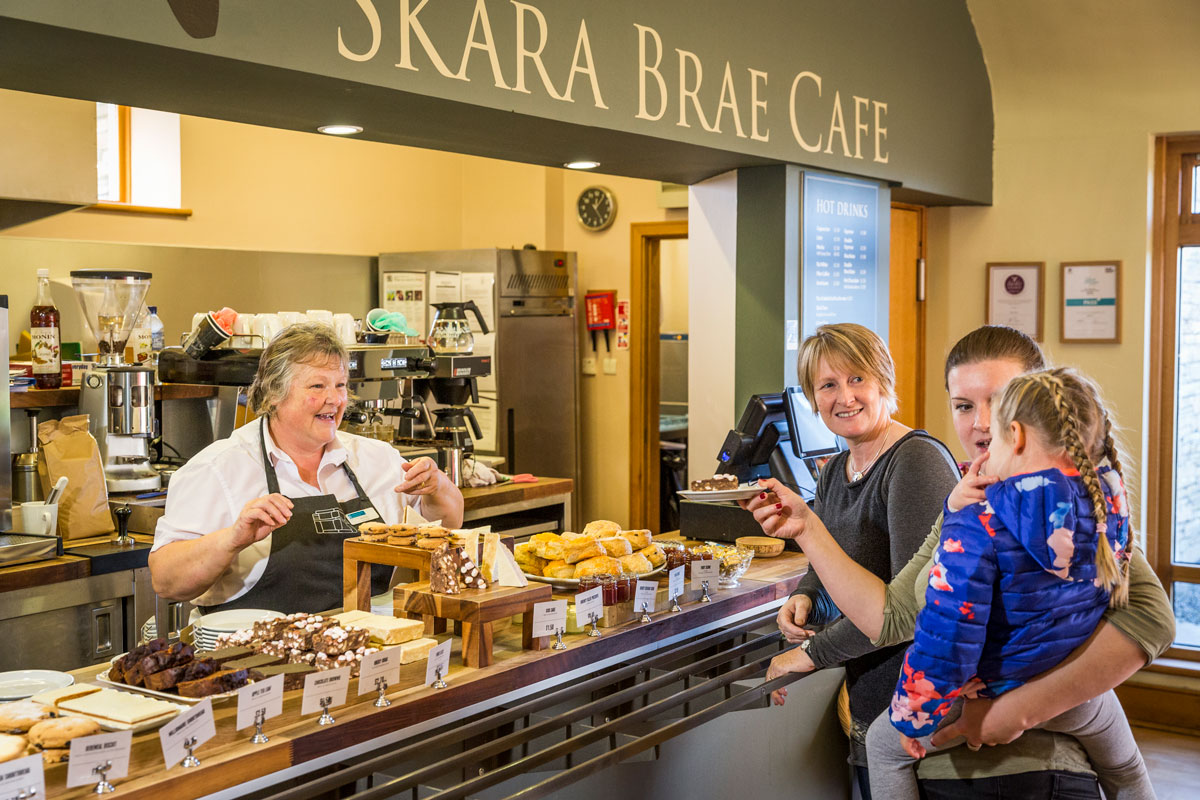 A family peruse an array of cakes and bakes at the Skara Brae cafe