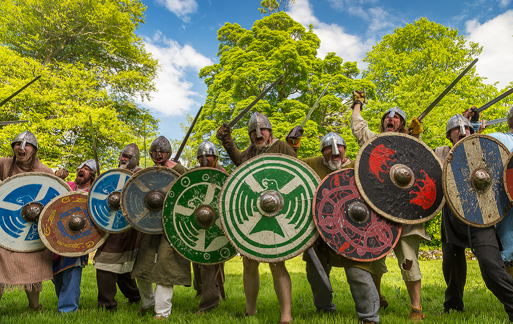 A group of reenactors dressed as Vikings posing menacingly with their swords and circular shields. Image © 2018 ColinCooperPhotography.com