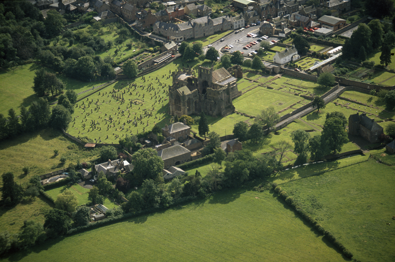 Aerial view of Melrose Abbey surrounded by green films