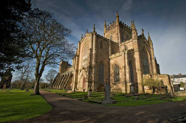 Exterior view of Dunfermline Abbey showing trees and garvestones in the foreground