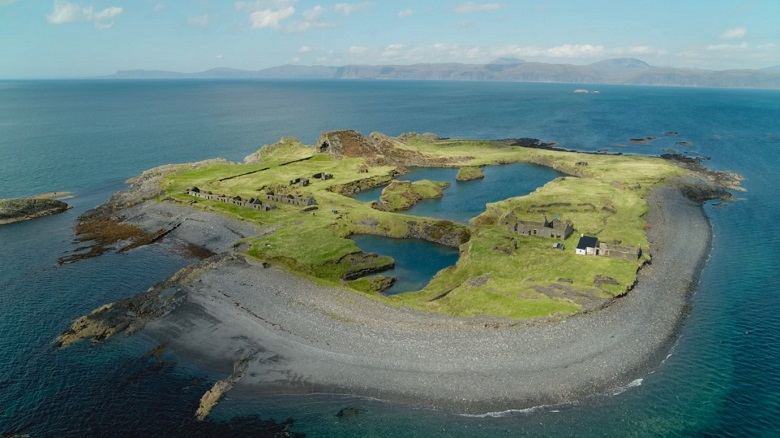 A small island with a curved shale beach and two small pools of water. The ruins of industrial buildings are dotted around the island.