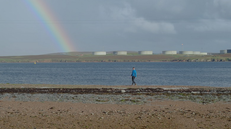 A man in a blue coat walks along a beach in front of large, round oil terminal buildings. A rainbow has formed in the background.