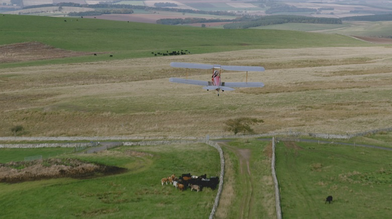 A Tiger Moth biplane flying over a straight Roam road flanked by drone stone walls
