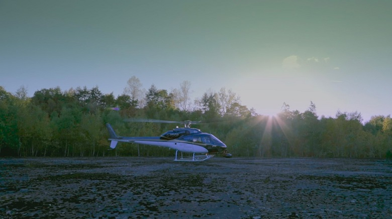 A helicopter landing on concrete with trees in the background