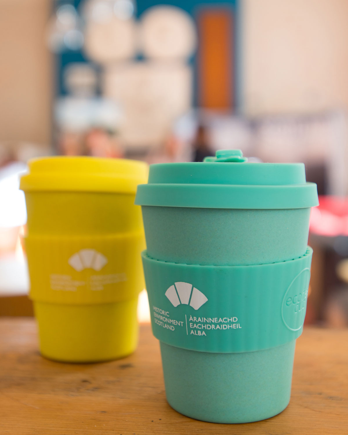 Two reusable cups, one green, one yellow, sit on a table in the Historic Environment Scotland cafe