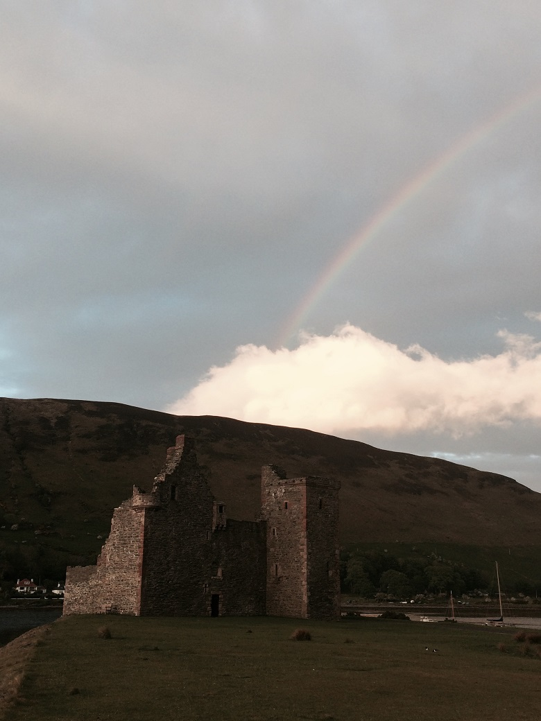 The ruins of a fortified tower house with a rainbow forming above it
