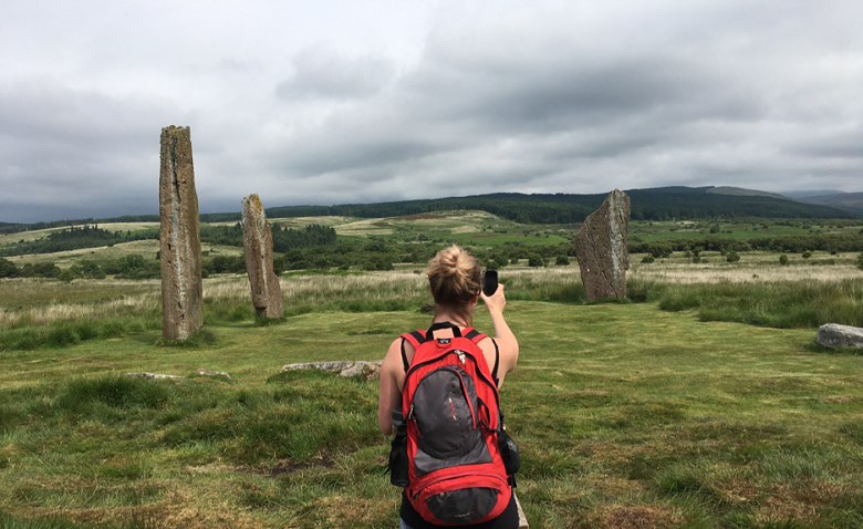 A lady wearing a rucksack takes a photo of three remote standing stones for Monument Monitor using a smartphone