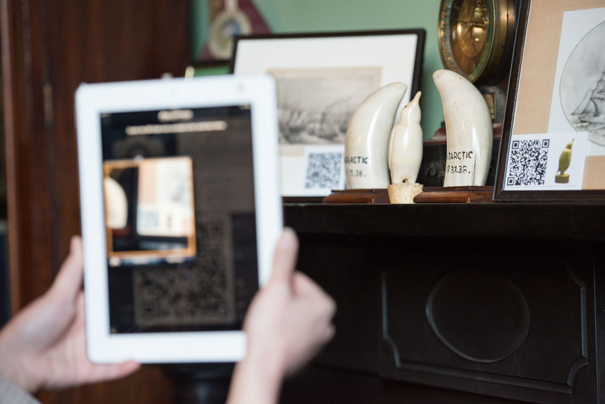 A visitor explores an exhibition using a tablet to scan a QR code