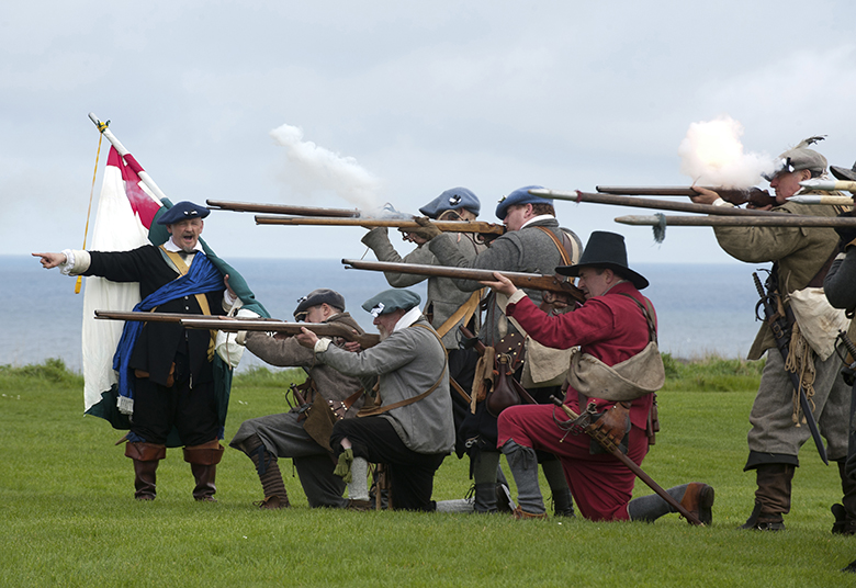Reenactors dressed as covenanters in tweeds and flat caps fire muskets