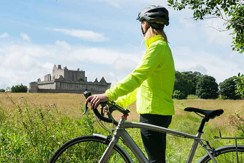 A person wearing a high vis jacket and bike helmet stands with a bike admiring Craigmillar Castle in the distance