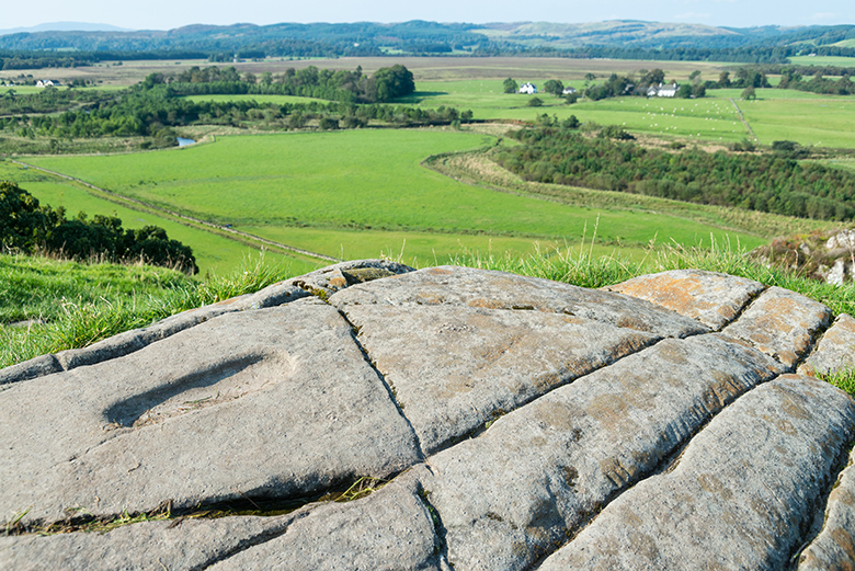 View out over a green rural landscape. There is a large rock in the foreground which has a footprint carved into it.