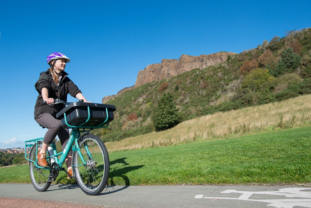 A lady cycling through Holyrood Park on a green bike.