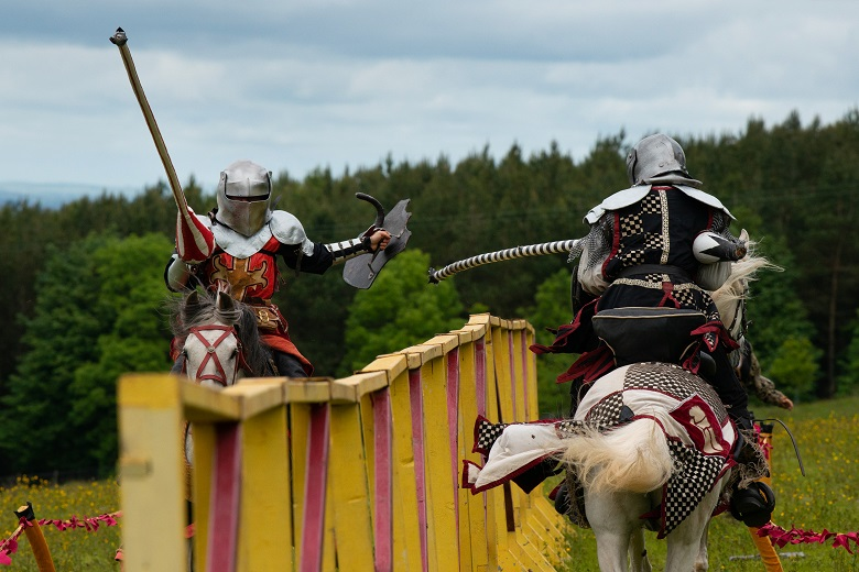 Action shot of two knights on horseback galloping towards each other with raised lances