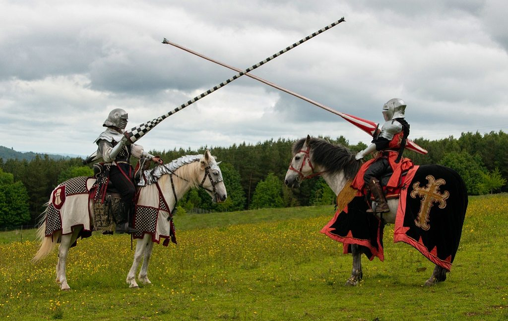 Two jousters on horseback cross lances against a grey sky. Both jousters and horses are colourfully attired with armour and heraldic symbols.