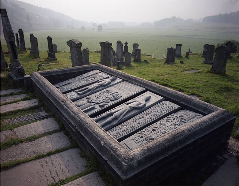 In the foreground there are grave slabs carved with warriors. Behind are upright grave stones. It is a misty day.