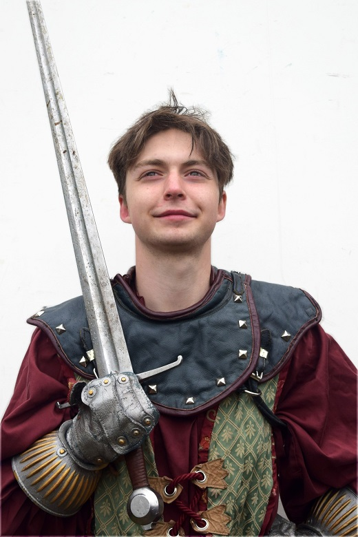A young, confident jousting knight wearing a red and black outfit and holding a sword