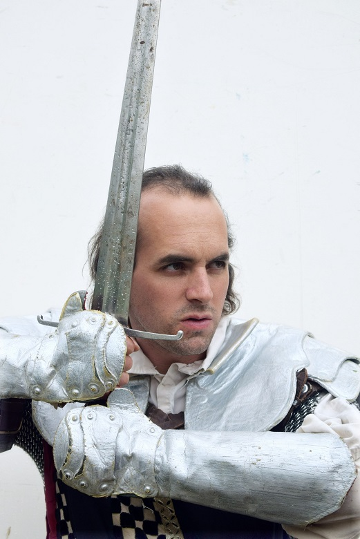 An angry looking knight wearing silver armour and grasping a sword with both hands
