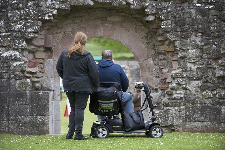 Visitors at Dryburgh Abbey look through an archway. One of the visitors is using a mobility scooter