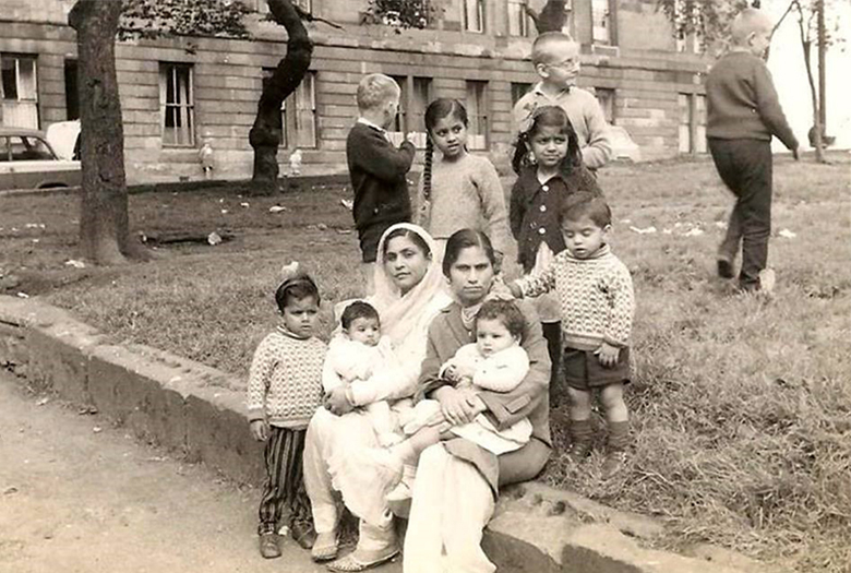 two women sit outside a tenement. Both hold babies. One wears a head scarf. They are surrounded by children.