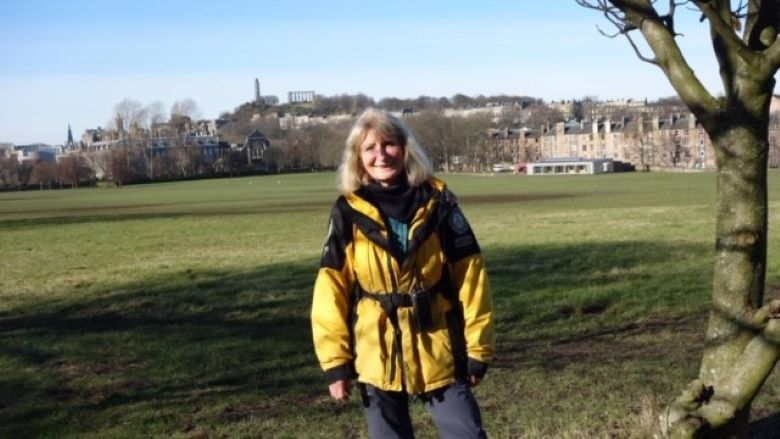 A lady wearing a black and yellow Ranger jacket stands in Holyrood Park with the education centre behind her