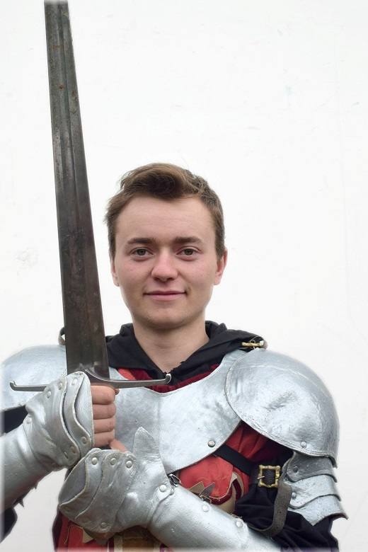 A young man wearing knight's armour posing with a large sword