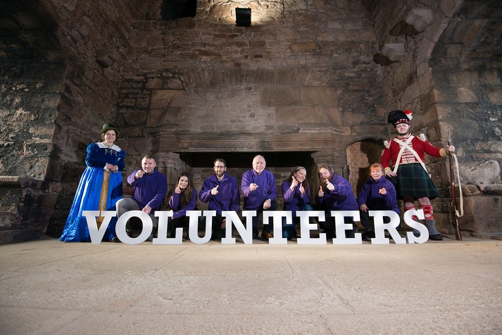 In an great hall in a castle, 7 people dressed in purple sweatshirts stand behind cut out letters spelling VOLUNTEERS. They are flanked by two people in historic costume - a renaissance woman and a redcoat