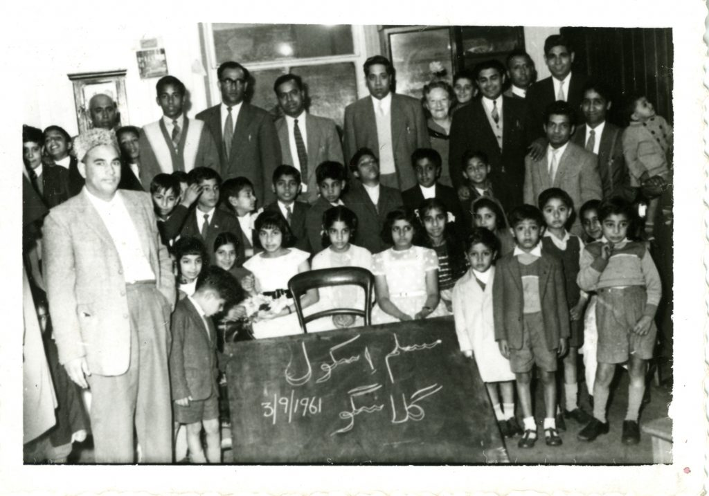 photo of a gathering of people. At the front there are two rows of children standing behind a blackboard with Arabic script and the date 3/9/1961 written on it. Everyone looks like they are wearing their best clothes.