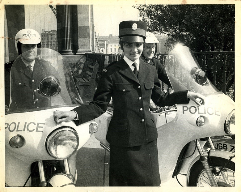 A woman wearing a police uniform stands in front of two police motorcycles