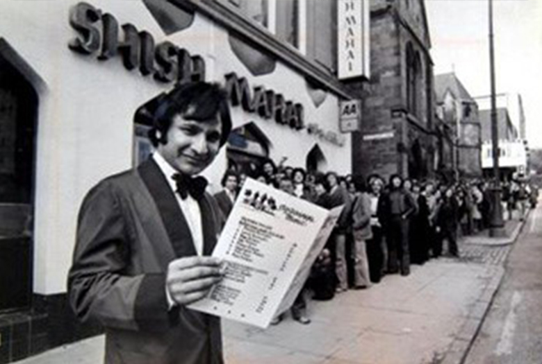 A huge queue outside the Shish Mahal restaurant. In the foreground, the proprietor smiles at the camera while holding a menu.