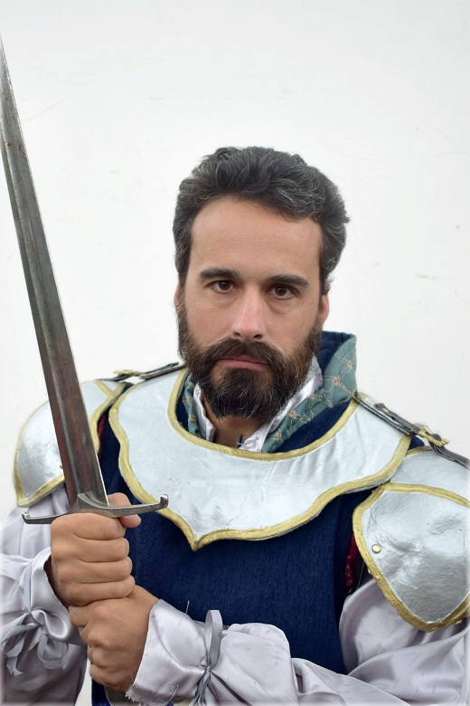 A bearded man wearing silver armour with a gold trim. He is posing menacingly with a sword.