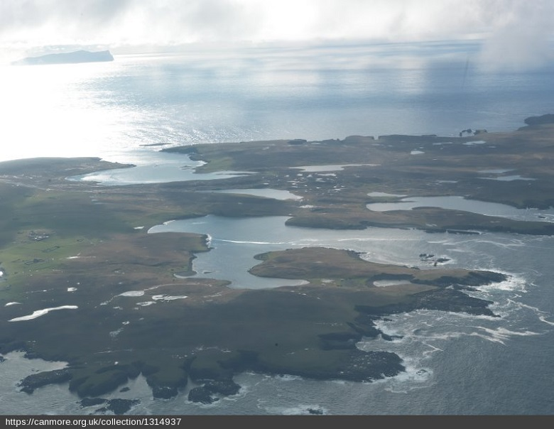 An aerial view of Papa Stour showing numerous bays and inlets, and the sun shining onto the sea in the background
