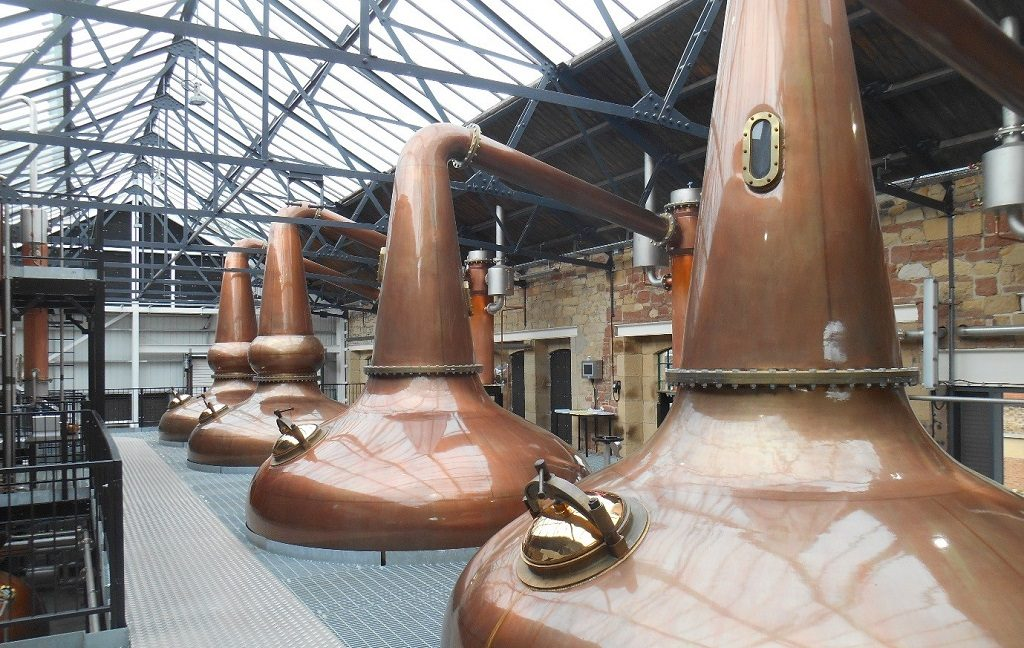 the interior of the Borders Distillery, Hawick. Copper whisky stills sit beneath a large glass ceiling.