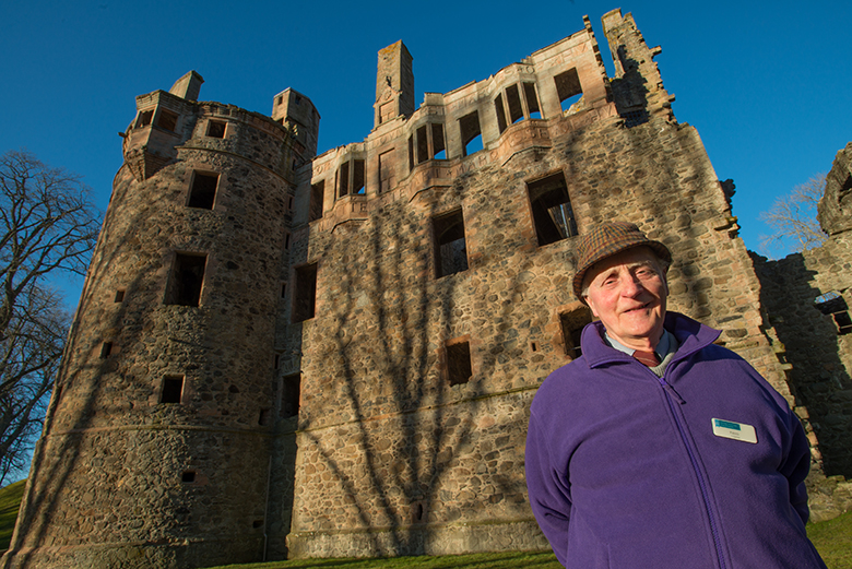 Patrick Scott, a volunteer guide at Huntly Castle, stands in front of the ruined castle in a purple sweater.