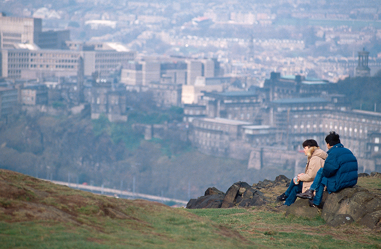 View from the top of Arthur Seat with visitors enjoying the view over Edinburgh