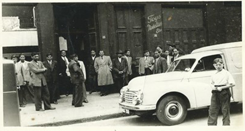 A number of South Asian men queue outside a building
