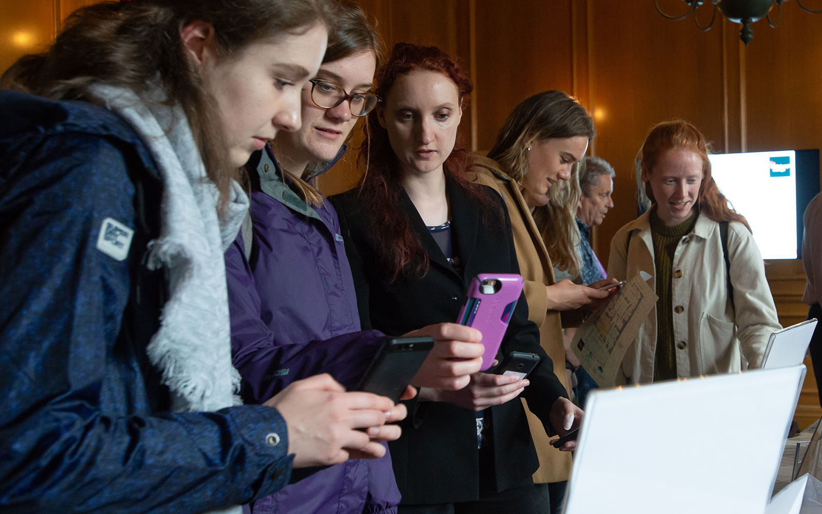 A group of visitors using their mobile phones to engage with augmented reality features at an interactive exhibition