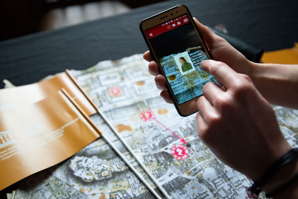A mobile phone activates augmented reality features from a map of Edinburgh's old and new towns